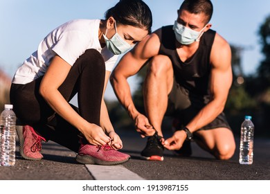 Athletic Asian couple wearing face mask while tying shoe laces with bottle of water on the road. Healthy lifestyle during covid-19 or coronavirus concept.