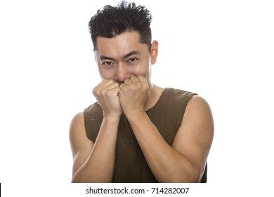 Athletic Asian male with trendy torn sleeveless shirt on a white background.  He is displaying shy expressions or gestures.  The handsome chinese or japanese man is muscular and physically fit
