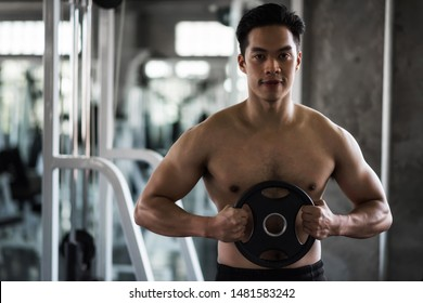 Athletic Asian muscle man with undressed nude torso holding disk weights in gym with equipment background and space for text. Fitness, sport, bodybuilding, training, motivation and lifestyle concept.