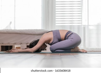 Athletic Asian woman practice yoga Child's pose to meditation in the morning Feeling so calm comfortable and relax,Healthcare and yoga at home Concept