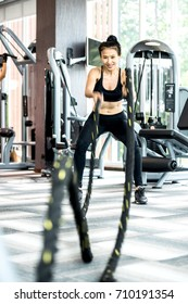Athletic Asian women with battle rope doing exercise in functional training fitness gym