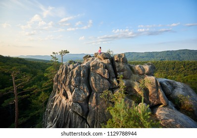 Athletic barefooted girl sitting in lotus pose on lit by summer morning sun top of huge rock on green mountains and clear blue sky background. Yoga, fitness and healthy lifestyle concept. Siddhasana