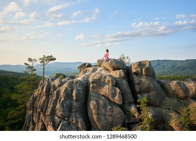 Athletic barefooted woman sitting in lotus pose on lit by summer sun top of huge rock on green mountains and clear blue sky background. Yoga, fitness and healthy lifestyle concept. Siddhasana