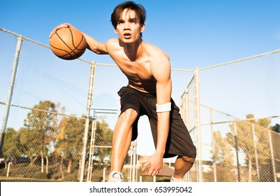 Athletic basketball player in action outdoors.