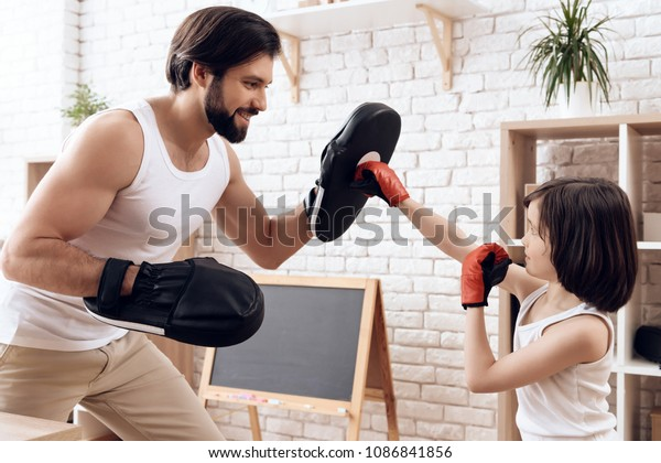 Athletic bearded father teaches son to box. Man coaches child to strike. Concept of self defense training.