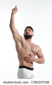 Athletic bearded man with a naked torso points with one hand upwards isolated on white background.