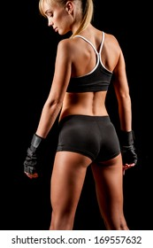 athletic beautiful blonde woman posing over dark background