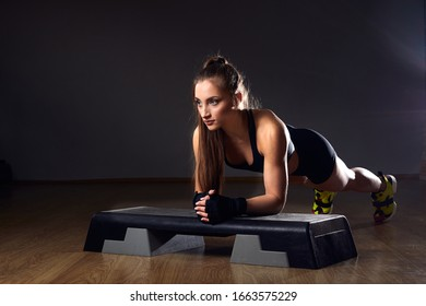 Athletic Beautiful Woman Does exercises - plank position.  Fitness and Bodybuilding Gym Training with Aerobic Step.