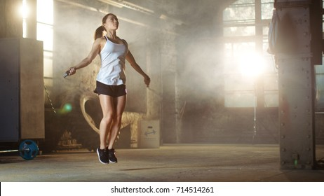 Athletic Beautiful Woman Exercises with Jump / Skipping Rope in a Gym. She's Covered in Sweat from Her Intense Fitness Training.