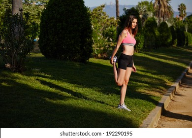 Athletic and beautiful young woman doing stretching before jogging in a very beautiful park with palm trees