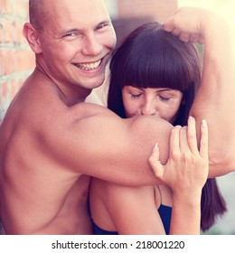 Athletic beauty man and sexy girl kissing hand