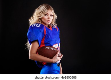 athletic blonde posing as american football girl on black background. Beautiful young woman wearing American football top holding ball. studio photo of american football woman