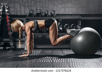 athletic blonde woman doing abs exercise in gym interior