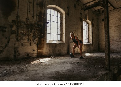 Athletic blonde woman swinging kettlebell  in an old building by the window