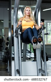 Athletic blonde woman  using press machine  in the gym