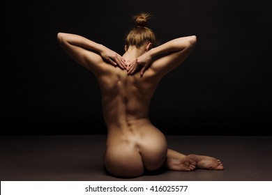 Athletic body of young woman over dark background. Yoga pose.  Bodyscape series.