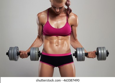 athletic bodybuilder woman with dumbbells.beautiful blonde girl with muscles.gym