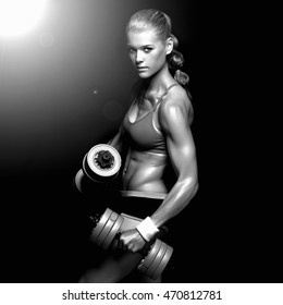 athletic bodybuilder woman with dumbbells.beautiful blonde girl with muscles.gym.monochrome portrait