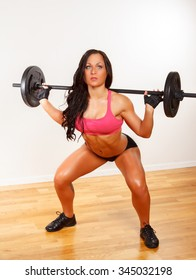 Athletic brunette woman in sexy sportswear doing exercises on legs with barbell.