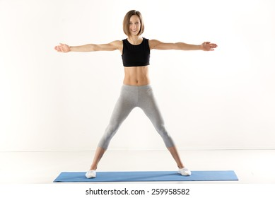 Athletic build women in sports clothes with arms outstretched, standing on the mat for exercise and with a smile looking at the camera.