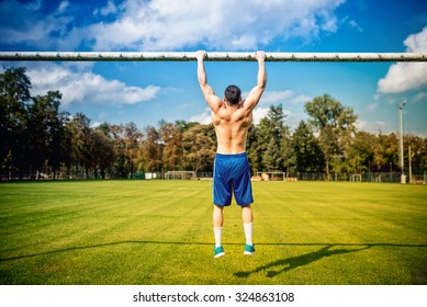 athletic built man doing chinups and core training in park. Fitness football player training on grass court, hardcore training