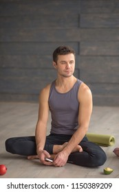Athletic caucasian man in sport wear relaxing after yoga class over grey studio background, sitting in lotus posture.
