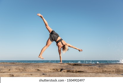 Athletic caucasian woman doing cartwheel on the beach with sea waves on background.