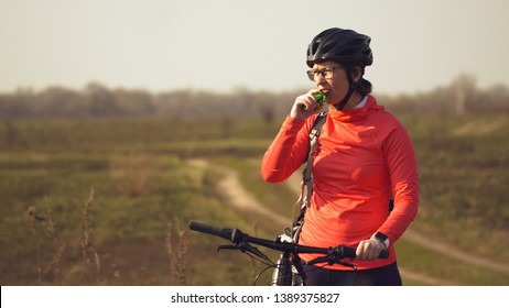 Athletic Caucasian woman eats protein bar ride on mountain bike on nature. Young sporty woman athlete in helmet resting while biting nutritional bar. Fitness woman eating energy snack outdoor.
