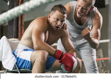 Athletic coach motivating tired boxer during fight on a ring