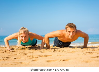 Athletic couple doing push ups on the beach, workout training