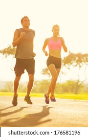 Athletic couple running together at Sunrise. Sport runners jogging on park trail in the early morning.  Healthy lifestyle fitness concept