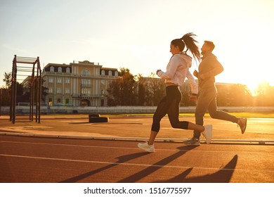 Athletic couple runs in the morning at the stadium.