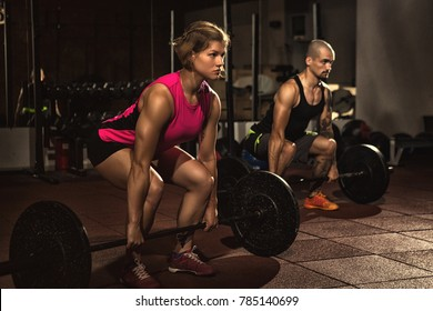 Athletic couple working out at crossfit gym doing deadlift exercise with heavy barbells fitness sport motivation people lifestyle strength muscles bodybuilding power determination sportspeople