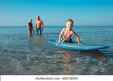 Athletic family with little boy teaching him surfing