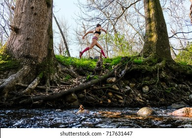 athletic fast female trail runner wearing pink running along a river with clear water between trees