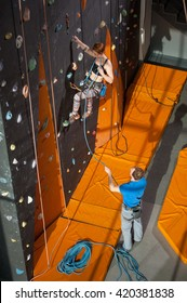 Athletic female climber is climbing on an indoor rock-climbing wall and male belayer standing on the ground insuring the climber