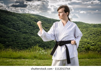 Athletic female dressed in kimono doing karate exercise outdoors. Martial arts.