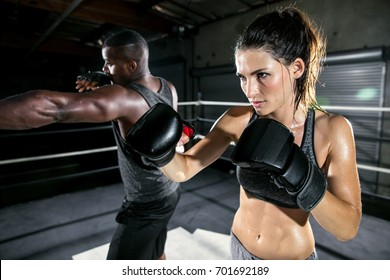 Athletic female fighter throws a jab during training session with her male trainer