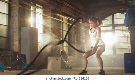 Athletic Female in a Gym Exercises with Battle Ropes During Her Fitness Workout/ High-Intensity Interval Training. She's Muscular and Sweaty, Gym is in Deserted Factory.