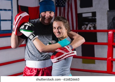 Athletic female hugs her coach in regular boxing ring in a gym