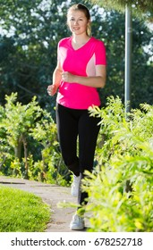 Athletic female in pink T-shirt is jogging in the park.