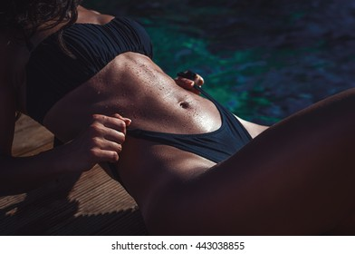 Athletic fit body woman in swimsuit sunbathing by the sea showing her perfectly shaped body and abs