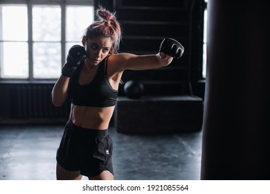 Athletic fit female boxer exercising punches with boxing bag in gym during kickboxing and self defense intensive workout