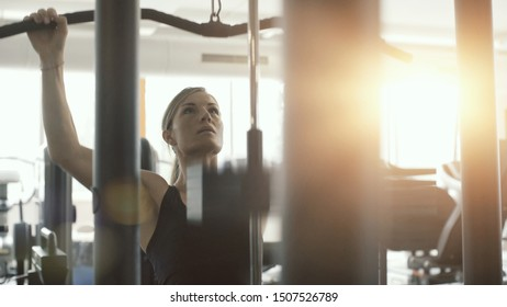 Athletic fit woman exercising at the gym, she is working out with a lat pulldown machine