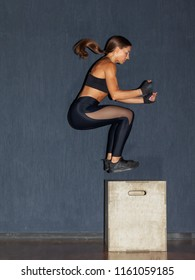 athletic fit woman jumping on crossfit box in gym