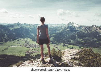 Athletic fit young woman hiker standing on a mountain summit admiring the green verdant alpine valley below her in a healthy active lifestyle and fitness concept
