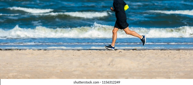 Athletic Fitness ManRunning on the Beach. Male Runner Jogging. Outdoor Workout. Fitness Concept.