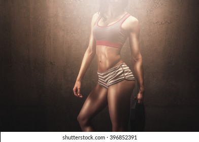 Athletic fitness model in fashion outfit holding weight iron plate and preparing for gym exercise while showing her fit and tight muscular body