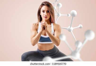 Athletic fitness woman standing near white molecule chain. Good metabolism concept.