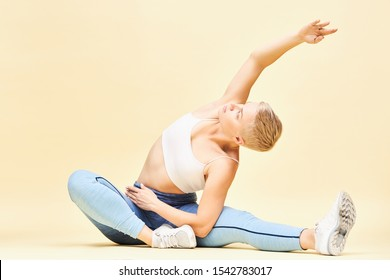 Athletic flexible young female in stylish sportswear doing yoga in seated position, side bending, expanding ribs, reaching one hand up. Boyish girl practicing pilates, sitting on floor, stretching